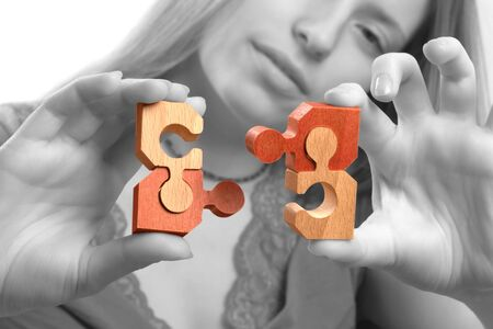 bringing: Young woman bringing together puzzle pieces. Monochrome gray background.