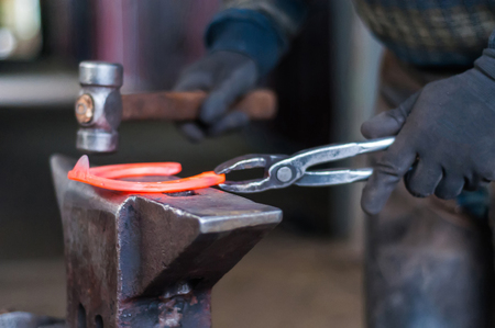 Blacksmith shaping the burning horse shoes before putting them up to the horses hooves. Imagens