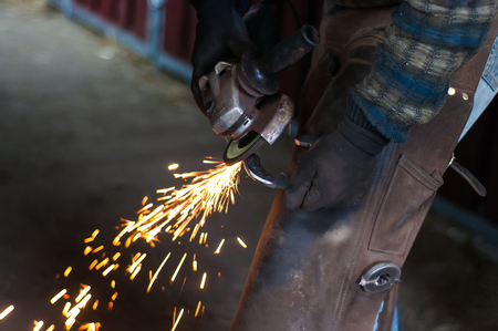 Blacksmith grinding the metal horse shoe peace to shape it. Imagens