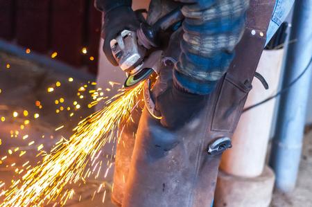 Blacksmith grinding the metal horse shoe peace to shape it. Фото со стока