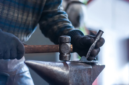 Blacksmith shaping the burning horse shoes before putting them up to the horses hooves.