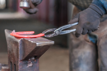 Blacksmith shaping the burning horse shoes before putting them up to the horses hooves. Standard-Bild