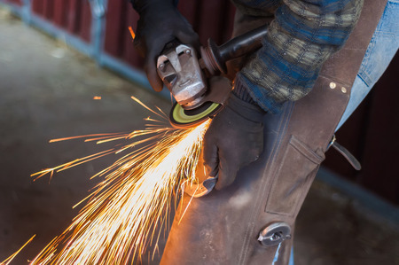 Blacksmith grinding the metal horse shoe peace to shape it. Archivio Fotografico