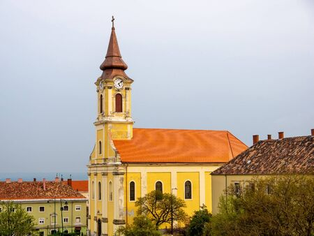 View on an old historic catholic church in Varpalota on a cloudy day.