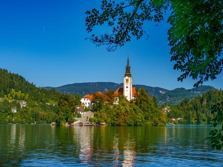 Uitzicht op de bedevaartskerk van de Hemelvaart van Maria aan het meer van Bled op een zonnige herfstdag.