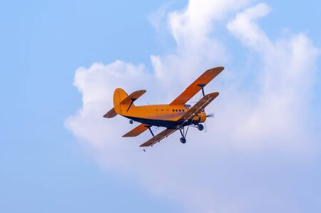 View on an old yellow plane flying againtst the blue sky on a sunny day