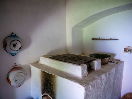 SZENTENDRE, HUNGARY - JUNE 8, 2019: View on a fireplace in a traditional hungarian pise house in the Skanzen of Szentendre, Hungary, Europe on sunny day.