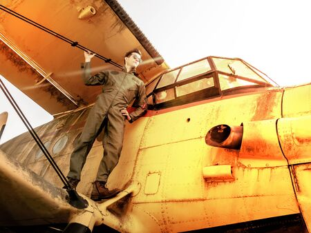 A handsome young man pilot in a green overall standing on the wing of an old plane on a sunny day.