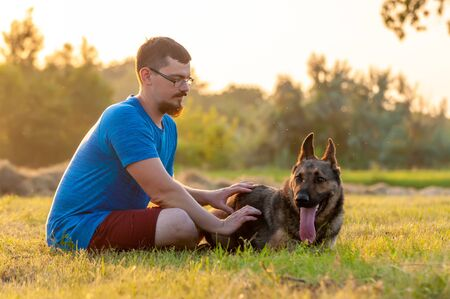 View on a handsome man and a german shepherd dog sitting and playing on the green grass during the sunset.