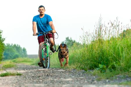 View on a handsome man on a bike while training a german shepherd dog. Stock Photo