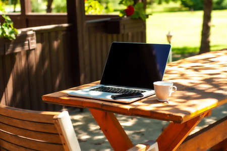 View on a laptop pc and a smartphone and acoffee mug on a table in the garden in a home office or home school enviroment on a sunny day. Stock Photo