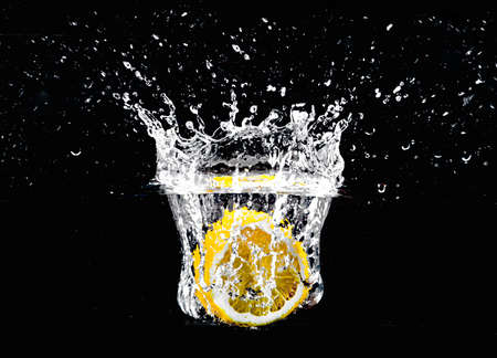 Creative photo of a half cut lemon splashing into the water in front of an isolated black background. Banque d'images