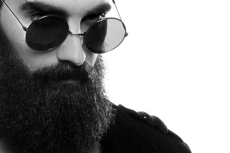 Closeup portrait of a bearded man wearing sunglasses in a studio environment in front of a white background.