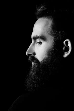 Portrait of a bearded man in a studio environment in front of a black background with dramatic low key lights. Banque d'images - 165640374