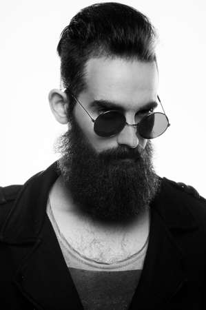 Fashion portrait of a bearded man wearing sunglasses in a studio environment in front of a white background. Banque d'images - 165640377