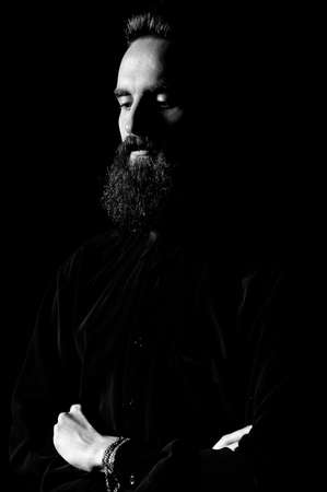 Portrait of a bearded man in a studio environment in front of a black background with dramatic low key lights. Banque d'images - 165640379