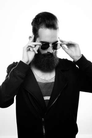 Fashion portrait of a bearded man wearing sunglasses in a studio environment in front of a white background. Banque d'images