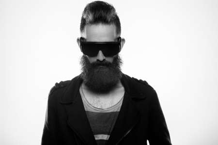 Fashion portrait of a bearded man wearing sunglasses in a studio environment in front of a white background. Banque d'images - 165640386