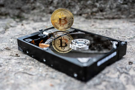 View on a hard disk drive with a bitcoin cryptocurrency on a concrete surface on a sunny day. Banque d'images