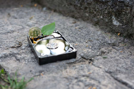 View on a hard disk drive with a bitcoin and a chia leaf representing the cryptocurrencies on a concrete surface on a sunny day. Banque d'images