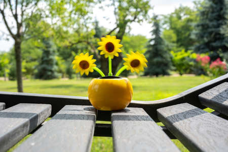 View on a solar powered plastic artificial sunflower moving by the sunlight representing a renewable energy source on a bench in the garden. Banque d'images
