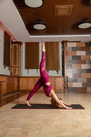 Young very attractive woman wearing red sports wear standing in yoga asana with raised leg against window.