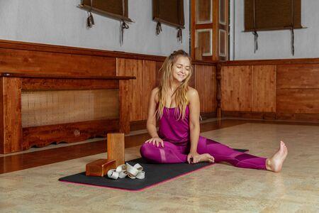 Yoga girl smiling while sitting on yoga mat