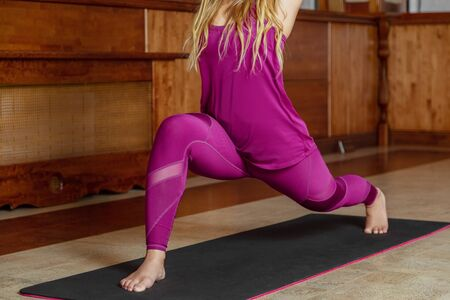 Young girl. Doing yoga or pilates exercise. Standing in Warrior one pose. Imagens