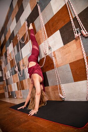Yoga girl dressed in a black sportswear is doing stretching on special rope equipment in the fitness center.