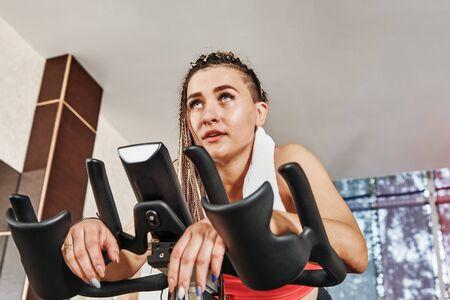 Moe meisje traint in de sportschool. Voor levensstijlontwerp. Fitness meisje opleiding. Gezonde levensstijl. Fitness training. Fitness cyclus. Fitnessapparatuur. Fitness instructeur meisje. Gewicht training.