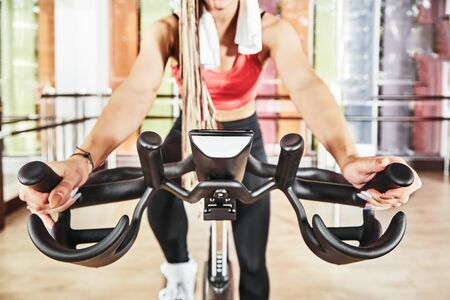 A cheerful young girl working out on a bike simulator at a fitness center. Bicycle simulator, great design for any purposes. Fitness training. Healthy lifestyle. Fitness cycle. Fitness workout. Cycle jersey.