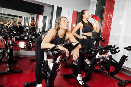Tired girls are training at the gym. For lifestyle design. Fitness girl training. Healthy lifestyle. Fitness workout. Fitness cycle. Fitness equipment. Fitness instructor girl. Weight training.