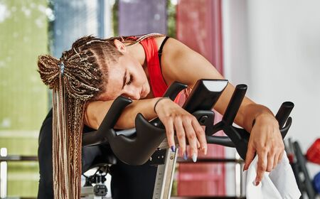 Tired girl are training at the gym. For lifestyle design. Fitness girl training. Healthy lifestyle. Fitness workout. Fitness cycle. Fitness equipment. Fitness instructor girl. Weight training. Фото со стока