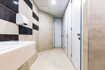Mens room with white porcelain urinals in line. Comfort male toilet urinal concept. Background clean. Interior element.