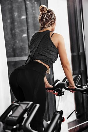 Modern with indoor cycling for healthy lifestyle design. Fitness equipment. Fitness workout. Side view. Fitness muscular body.
