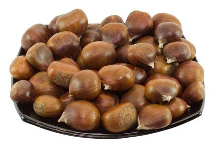 Chestnuts on dark plate isolated on white background