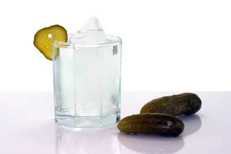 Vodka with ice in glass and salt cucumbers isolated on mirror surface Stock Photo