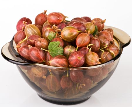 Gooseberries in bowl on light background