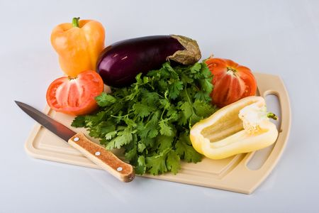 Vegetables on chopping board on light background photo