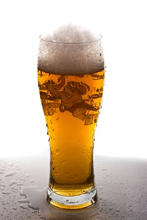 Light beer in tall glass on wet surface with white background photo