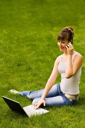Happy young woman with notebook and mobile phone on the grass Stock Photo