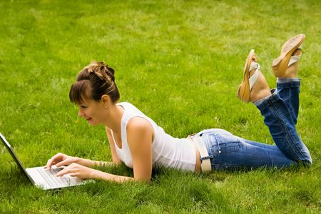 Happy young woman with notebook on the grass