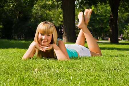 Young smiling girl lies on grass