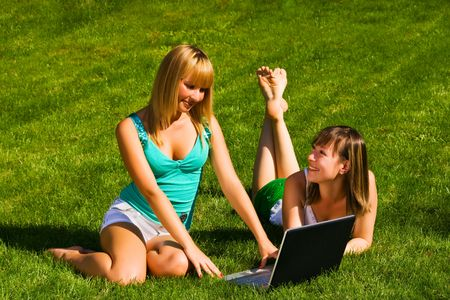 Two young girls on the grass with notebook Stock Photo