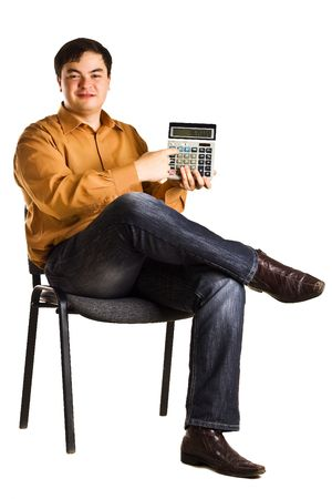 Young man sitting on a chair shows the numbers on the calculator (isolated on white background)