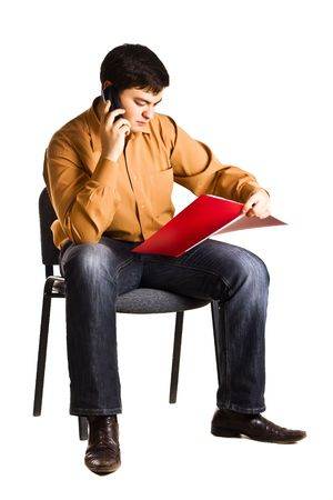 Young man sitting on a chair talking on the phone and examine documents in the red folder (isolated on white background)