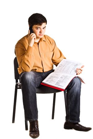 Young man sitting on a chair talking on the phone and examine documents in the red folder (isolated on white background) Stock Photo - 6383458