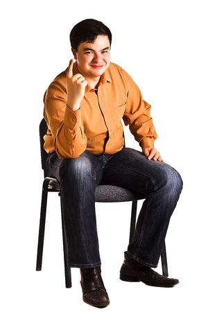 Young man sitting on a chair shows the finger (isolated on white background)