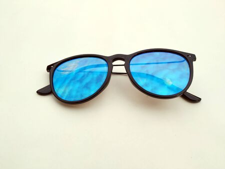 Children sunglasses, sun shades or spectacles isolated on light yellow  background. Color child glasses protection from sun and UV rays. Concept of sun protection and vacation.
