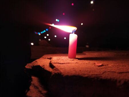 A CANDLE FLAME GIVE LIGHT IN DARK NIGHT WITH BLINKING LIGHTS